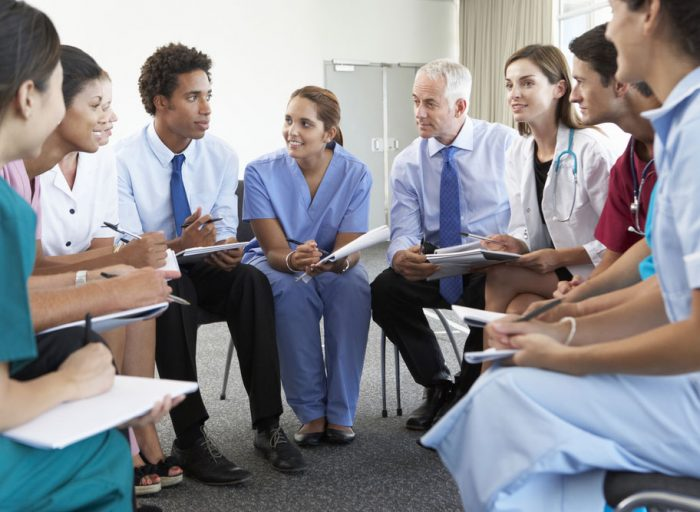 Principle three of team-based care: the daily huddle, such as this group of medical professional seated in a tight circle